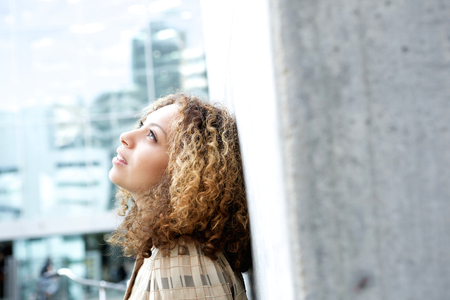 Close up portrait of a beautiful young woman looking up and thinking outdoors