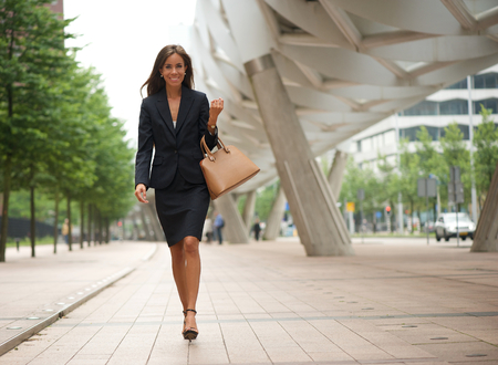Photo for Portrait of a business woman walking in the city with handbag - Royalty Free Image