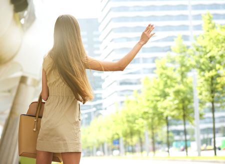 Photo for Young woman from behind with raised arm waving for taxi in the city - Royalty Free Image