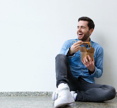 Photo for Portrait of an attractive  young man eating chinese food with chopsticks - Royalty Free Image