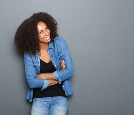Photo pour Portrait of a happy young african american woman posing with arms crossed - image libre de droit