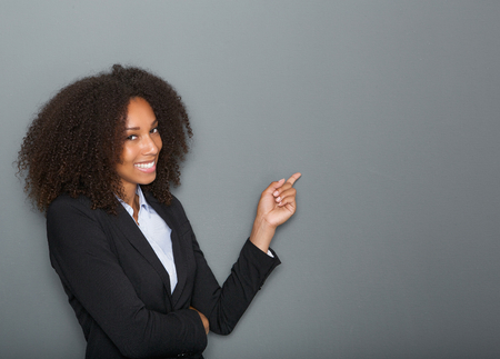 Close up portrait of a friendly business woman pointing finger on gray background