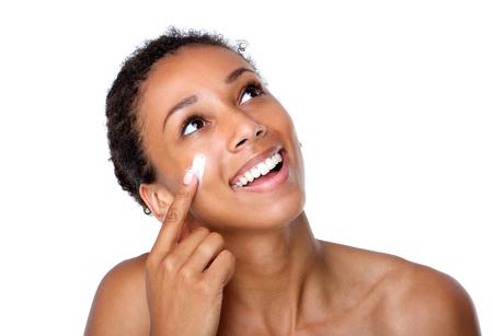 Photo pour Close up portrait of a smiling woman applying lotion on face - image libre de droit