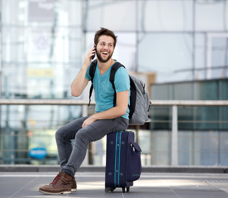 Foto de Portrait of a happy young man calling by mobile phone at airport - Imagen libre de derechos