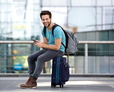 Foto de Portrait of a young man sitting on suitcase and sending text message - Imagen libre de derechos