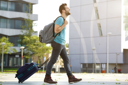 Photo for Profile portrait of a young man walking with suitcase and bag - Royalty Free Image