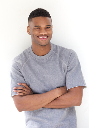 Photo for Portrait of a cool young black man smiling with arms crossed on white background - Royalty Free Image