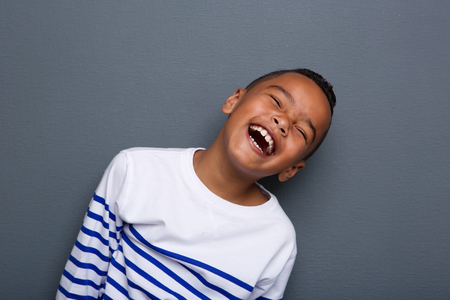 Foto de Close up portrait of a happy little boy smiling on gray background  - Imagen libre de derechos