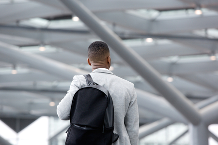 Photo for Rear view portrait of a black man standing in airport with bag - Royalty Free Image