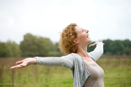 Foto de Close up portrait of a cheerful carefree woman with arms outstretched - Imagen libre de derechos
