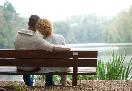 Foto de Rear view of a happy couple sitting together on bench outdoors - Imagen libre de derechos