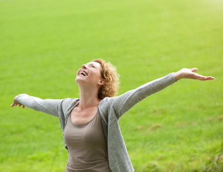Photo pour Portrait of a cheerful older woman smiling with arms outstretched  - image libre de droit
