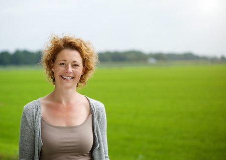 Foto per Portrait of an attractive woman smiling outdoors by green countryside  - Immagine Royalty Free
