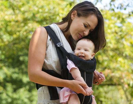 Foto de Portrait of a happy mother kissing baby on the head - Imagen libre de derechos