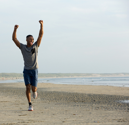 Photo pour Young black man running on beach with arms raised up in celebration - image libre de droit