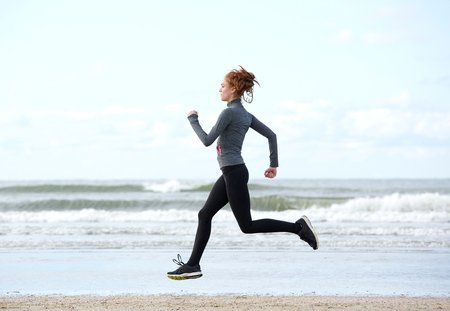 Horizontal side view of a healthy young woman running at the beach