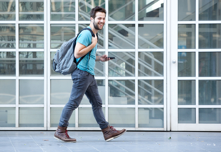 Photo for Side view portrait of a young man walking on sidewalk with mobile phone and bag - Royalty Free Image