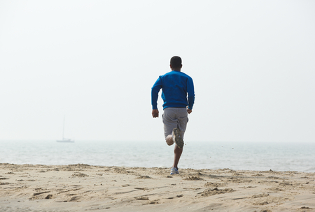 Photo for Rear view african american man running on the beach - Royalty Free Image