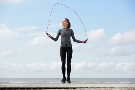 Photo for Healthy young woman with jump rope at the beach - Royalty Free Image