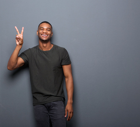 Photo pour Portrait of a young man smiling showing hand peace sign - image libre de droit