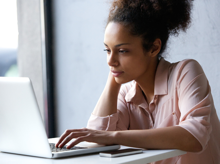 Photo for Close up portrait of a young black woman looking at laptop - Royalty Free Image
