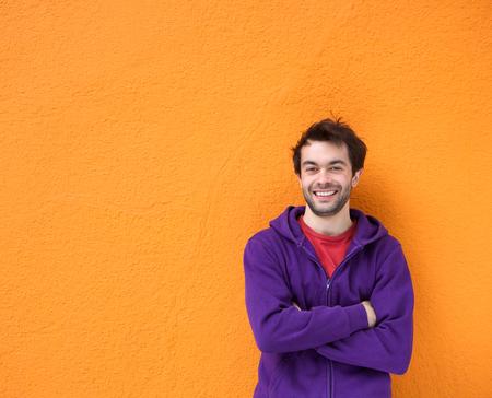 Photo pour Portrait of a confident young man smiling with arms crossed - image libre de droit