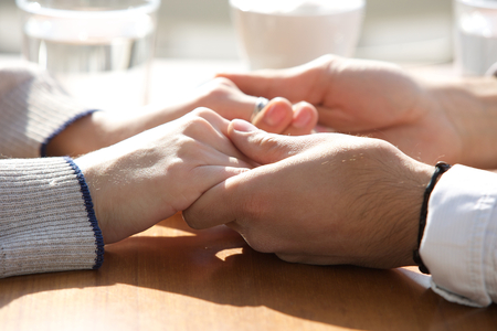 Photo for Close up male and female holding hands over table - Royalty Free Image