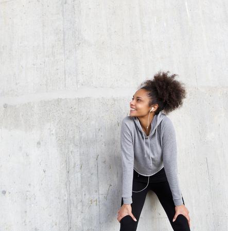 Foto de Close up portrait of an attractive young fitness woman smiling with earphones - Imagen libre de derechos