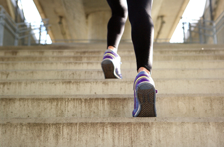 Photo pour Rear view sports female running up stairs - image libre de droit