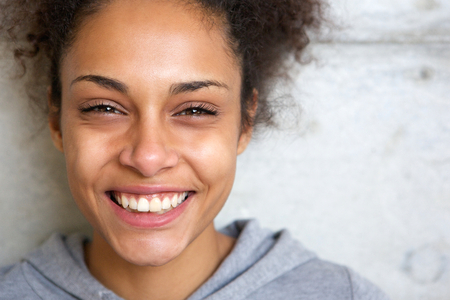 Photo pour Close up portrait of a beautiful young african american woman smiling - image libre de droit
