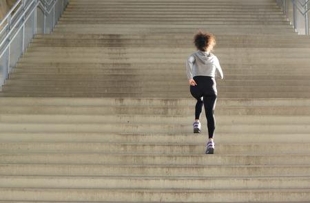 Foto de Rear view young female athlete running up stairs - Imagen libre de derechos
