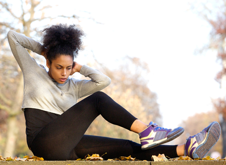 Young african american woman exercising sit ups outdoors