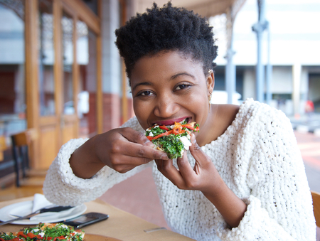 Photo for Close up portrait of an happy african american woman eating pizza - Royalty Free Image