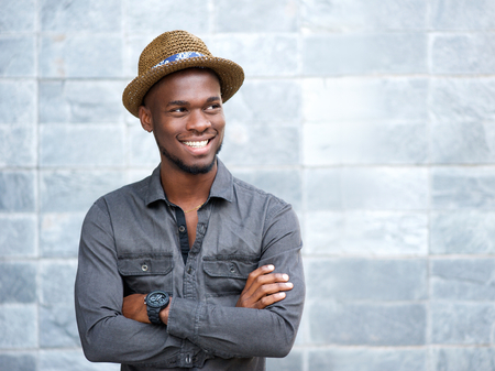Photo pour Close up portrait of a happy african american guy smiling with arms crossed - image libre de droit