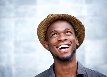 Foto de Close up portrait of a cheerful young man laughing and looking up - Imagen libre de derechos