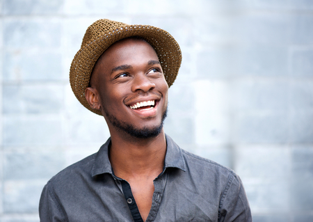 Foto de Close up portrait of a happy young african american man laughing against gray background - Imagen libre de derechos