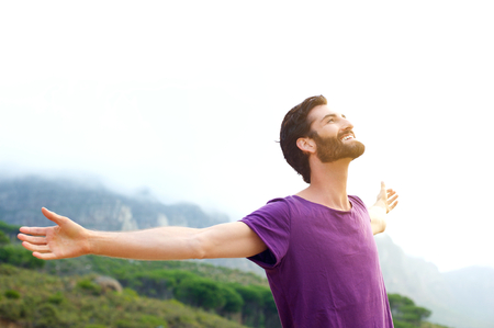 Photo for Portrait of a happy young man standing in nature with arms spread open - Royalty Free Image