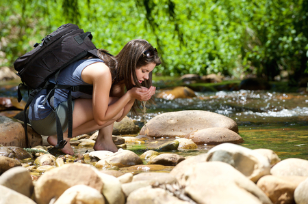 Photo for Young woman drinking water from outdoor stream with her hands - Royalty Free Image