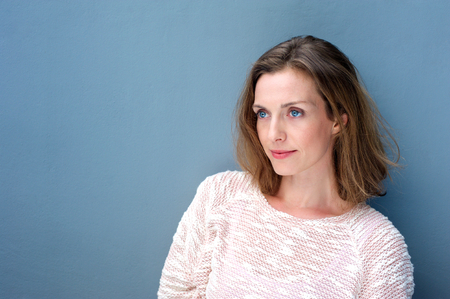 Foto per Close up portrait of a charming woman in sweater posing on blue background - Immagine Royalty Free