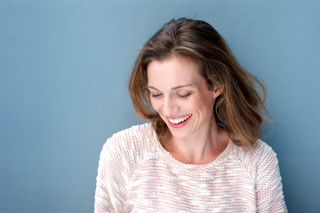 Foto de Close up portrait of a beautiful mid adult woman laughing with sweater - Imagen libre de derechos