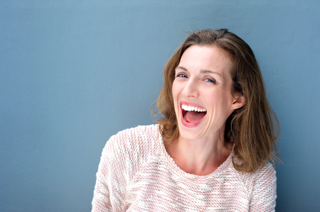 Photo pour Close up portrait of a happy beautiful fresh mid adult woman laughing on blue background - image libre de droit