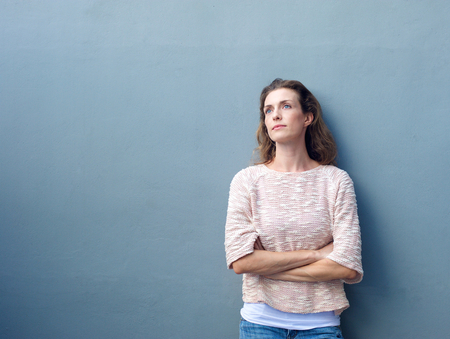 Foto de Portrait of an attractive woman posing with arms crossed looking away with thoughtful expression - Imagen libre de derechos