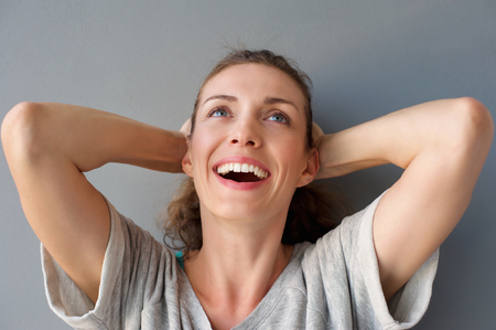 Foto für Close up portrait of a carefree happy woman laughing with hands in hair against gray background - Lizenzfreies Bild