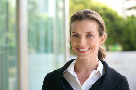 Photo pour Close up portrait of a smiling business woman with black jacket and white shirt standing outside - image libre de droit
