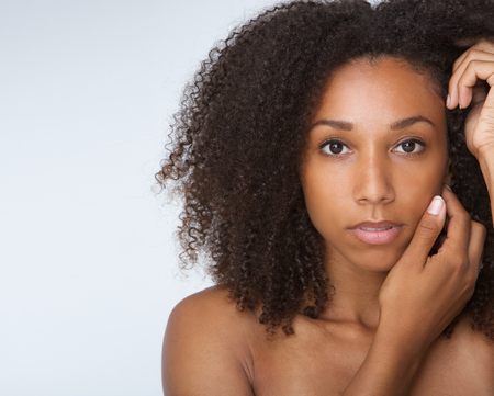 Photo pour Close up portrait of an african american female fashion model posing with hands by face - image libre de droit