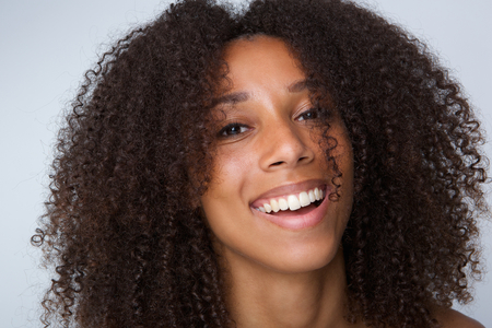 Foto de Close up portrait of a happy african american woman with curly hair laughing - Imagen libre de derechos
