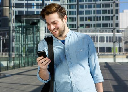 Foto de Portrait of a happy young man sending text message from mobile phone at the airport - Imagen libre de derechos