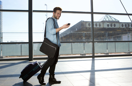 Photo for Full body portrait of a happy male traveler walking with bags and cellphone - Royalty Free Image