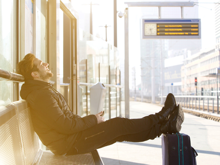 Foto de Side view portrait of a happy young man sitting with travel bag at the train station - Imagen libre de derechos