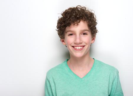 Photo pour Close up portrait of a happy young boy with curly hair smiling against white background - image libre de droit